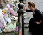 A woman lays flowers for the victims of the Manchester Arena attack, in central Manchester, Britain May 23, 2017.