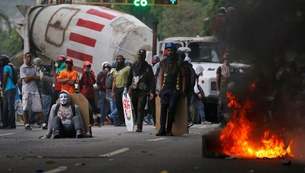 Demonstrators stand near a truck as they use it as a barricade during anti-government protests in Caracas, Venezuela.