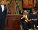 Rafael Correa stands next to President Lenin Moreno after handing him the presidential sash as National Assembly head Jose Serrano looks on.