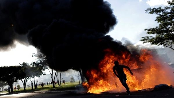 A demonstrator runs near a burning barricade during a protest against President Michel Temer and the latest corruption scandal to hit the country, in Brasilia.