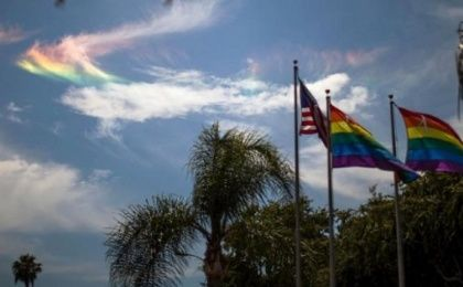 A rainbow is seen in the sky behind LGBT pride flags and the U.S. flag in West Hollywood, California, United States, June 26, 2015.