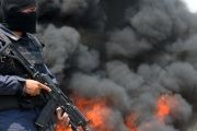 A police officer stands guard as nearly 400 kg of cocaine burn in Tegucigalpa, Honduras.