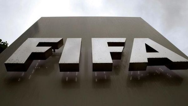 Raindrops flow down on a logo in front of FIFA