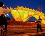 People take pictures of the ''Golden Bridge on Silk Road'' installation by artist Shu Yong, set up ahead of the Belt and Road Forum in Beijing, China May 10, 2017.