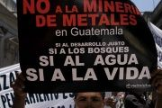 A demonstrator carries a sign protesting metals mining in Guatemala in defense of water and life in Guatemala City in 2006.