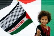 A young girl holds up a Palestinian flag.