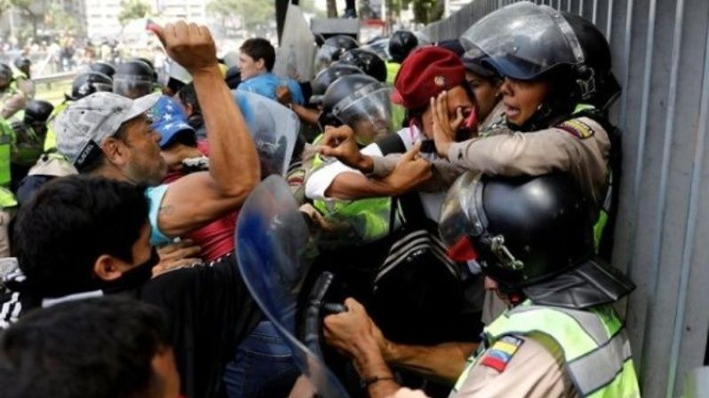 Demonstrators scuffle with security forces during an opposition rally in Caracas, Venezuela, amid ongoing anti-government protests.