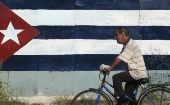 Man rides by Cuban flag.