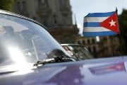 A Cuban flag flies attached to a vintage car in Havana.