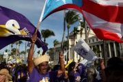A member of a labor union shouts slogans while holding a Puerto Rico flag during a protest against austerity plans.