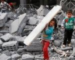 Children collect items from among the debris of a school for the deaf and mute, destroyed in what activists said were overnight US-led airstrikes against ISIS.