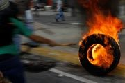 A tire is set to fire by opposition protesters, May 31, 2017.