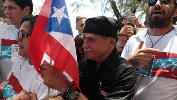 Puerto Rican Oscar Lopez Rivera (C) carries a national flag as he meets with supporters after being released from house arrest May 17, 2017.