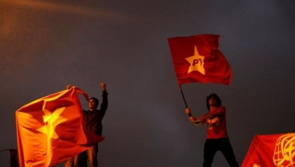 Protesters wave the Workers Party flag in a protest against unelected President Michel Temer.