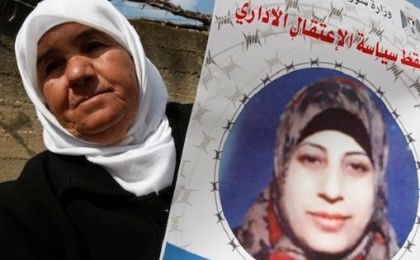 The mother of Hana Shalabi, a hunger-striking Palestinian prisoner, holds up an image of her daughter.
