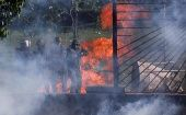 Riot security forces look through an air base fence destroyed by demonstrators rallying against Venezuela