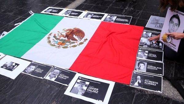 Photos of murdered journalists border the Mexican flag in a protest against the 106 reporters who fell victim to the mass killings in Mexico since 2000.