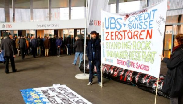 Protesters display a banner to protest against the financing of the Dakota Access oil pipeline by Swiss banks UBS and Credit Suisse as participants arrive ahead of the annual shareholder meeting of Swiss bank UBS in Basel, Switzerland.