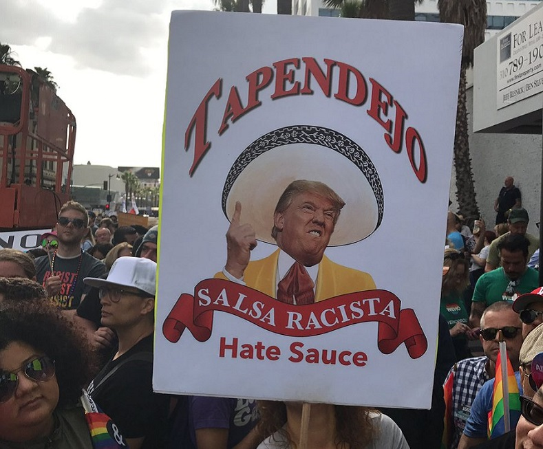 "A placard pokes fun at Trump and his ""hate sauce."""