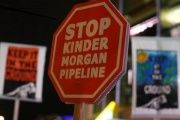 Protesters hold up signs in opposition to Canada's decision to approve Kinder Morgan Inc's pipeline, November 29, 2016.