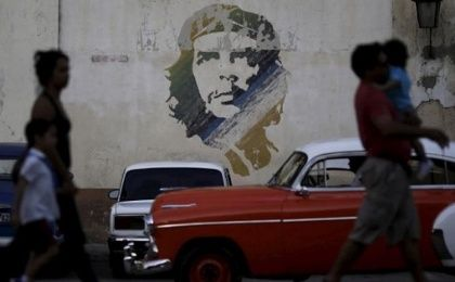 People walk past a painting of late revolutionary hero Ernesto