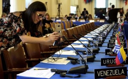 A woman takes pictures of delegates seats before the Organization of American States (OAS) meeting of foreign ministers to discuss the situation in Venezuela in Washington, U.S., May 31, 2017.