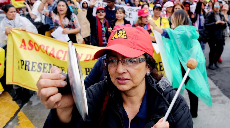Esta mujer colombiana expresa su inconformidad golpeando la tapa de una cacerola durante la marcha que forma parte de las protestas de los educadores para reclamar mejoras laborales en Bogotá, Colombia.