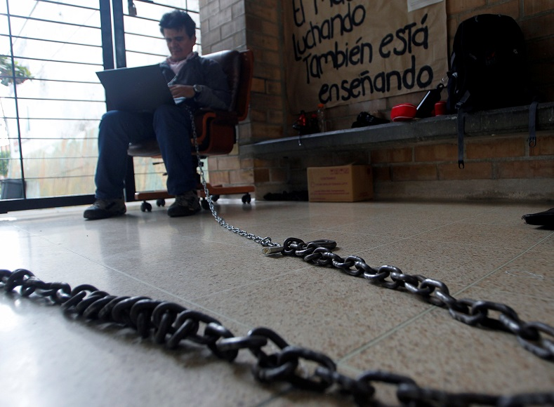 Colombian teacher Carlos Fredy has chained himself to the door of a school in Medellin to protest poor infrastructure at Colombian schools.