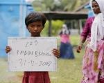 A Rohingya migrant mother stands nearby as her child holds a placard while posing for photographs for immigration purposes.