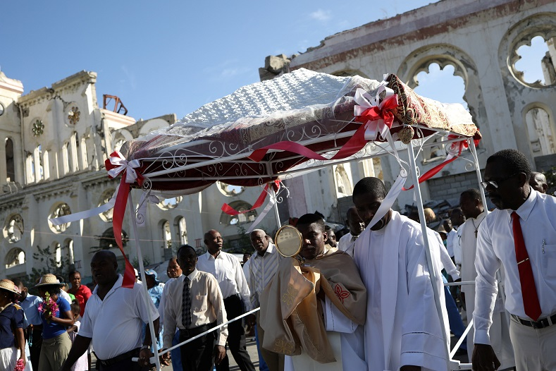Mass and a procession, are the two universal features of the celebration. This parade goes past the ruins of Our Lady of Assumption Cathedral in Port-a-Prince, Haiti