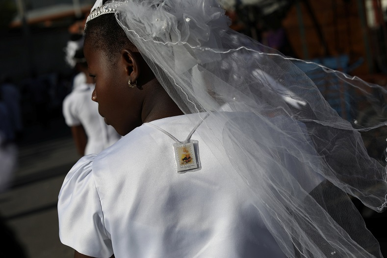 A young girl dressed in white, and wearing a scapular, takes part in Corpus Christi celebrations in Haiti. Judging by her dress, she made First Communion recently