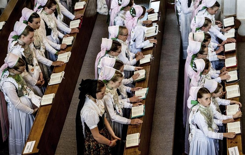 Young girls wearing traditional dress attend mass at a church in Crostwitz, Germany
