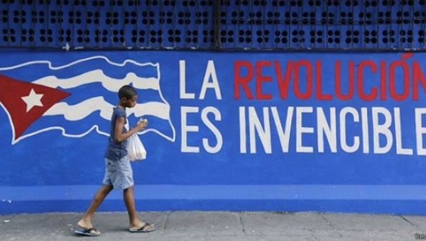 "A Cuban child walks past a mural that reads, ""The Revolution is Invincible."""