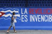 A Cuban child walks past a mural that reads,