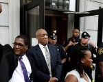 Actor Bill Cosby (C) stands as his publicist Andrew Wyatt raises his fist after a judge declared a mistrial in Cosby's trial in Norristown, Pennsylvania, U.S., June 17, 2017.