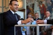 French President Emmanuel Macron casts his ballot as he votes at a polling station in the second round parliamentary elections in Le Touquet.