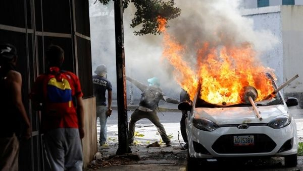 Protesters next to a burning car during a protest against the government in Caracas, June 14, 2017.