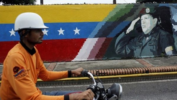 A motorcyclist rides past a mural depicting Venezuela