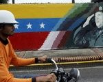 A motorcyclist rides past a mural depicting Venezuela's late President Hugo Chavez in Sabaneta, Venezuela, June 13, 2017.