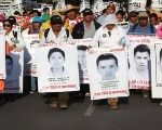 Family members march with pictures of the disappeared 43 Ayotzinapa students