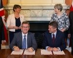 Prime Minister Theresa May next to DUP leader Arlene Foster, as DUP MP Jeffrey Donaldson signs paperwork with Britain's Parliamentary Secretary to the Treasury, Gavin Williamson.