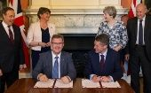 Prime Minister Theresa May next to DUP leader Arlene Foster, as DUP MP Jeffrey Donaldson signs paperwork with Britain