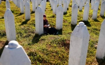 Bosnian Muslim woman prays near a grave before mass funeral in Memorial Center in Potocari near Srebrenica, Bosnia and Herzegovina July 11, 2016.