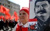 A Russian Communist party activist carries a portrait of late Soviet leader Joseph Stalin during a May Day rally in Moscow on May 1, 2017.