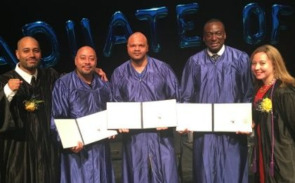 The men, now in their 40s, were clad in blue graduation gowns at Monday