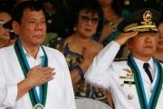 Philippine Pesident Rodrigo Duterte (l) stands to attention next to new Armed Forces chief General Eduardo Ano during the singing of Philippine national anthem at a military camp in Quezon city, Metro Manila, December 7, 2016.