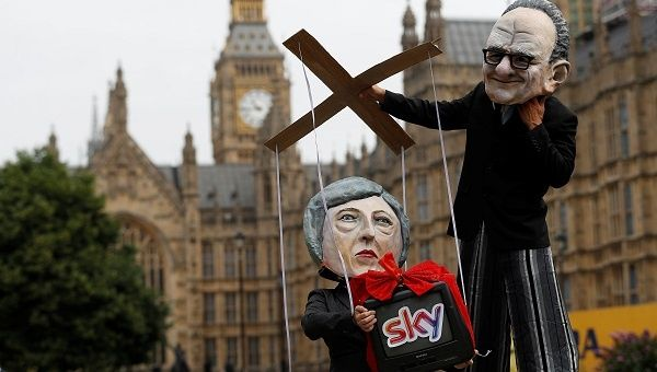 Performers pose outside the Houses of Parliament, wearing puppet heads of media mogul Rupert Murdoch and UK Prime Minister Theresa May in London, UK June 29, 2017