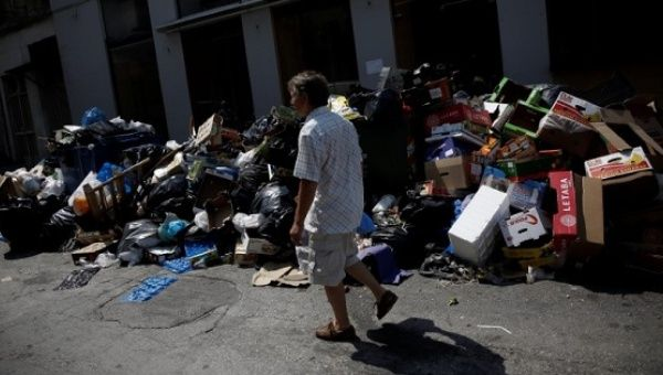 A man walks past a pile of garbage in Piraeus, near Athens, Greece, on June 26, 2017.