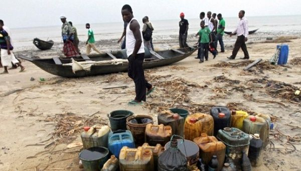Villagers walk past jerrycans containing crude oil at the shore of the Atlantic ocean near Orobiri village, in Warri, Nigeria, on December 31, 2011.