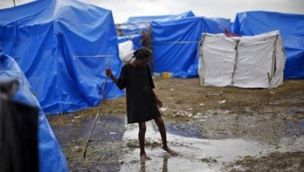 A girl crosses a puddle of water after heavy rains at a makeshift tent c& in & Organization Improves Sanitation in Haiti With Compost Toilets ...